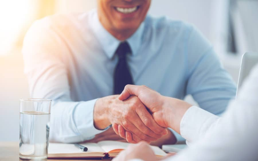 stock-photo-good-deal-close-up-of-two-business-people-shaking-hands-while-sitting-at-the-working-place-400222735