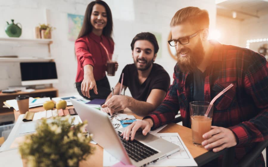 stock-photo-two-guys-and-a-girl-are-drinking-juice-in-the-office-they-sit-at-a-table-with-a-computer-and-790590634