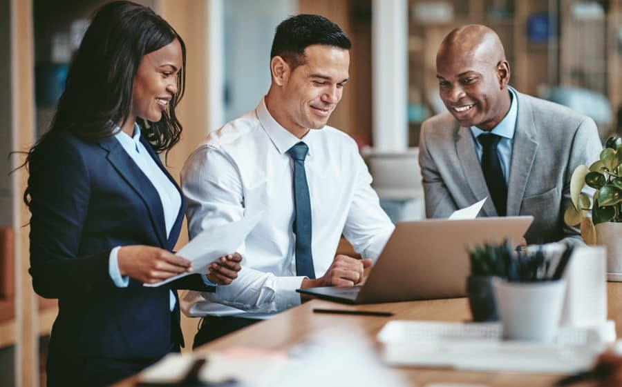 stock-photo-smiling-group-of-diverse-businesspeople-going-over-paperwork-together-and-working-on-a-laptop-at-a-1477775183